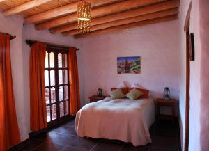 A bed or beds in a room at Hostal Antigua Tilcara