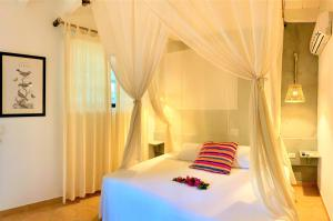 A bed or beds in a room at Hotel Fenix Beach Cartagena