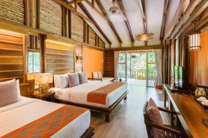 A bed or beds in a room at Home Phutoey River Kwai Hotspring & Nature Resort - SHA Certified