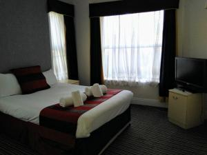 A bed or beds in a room at The Crown Hotel