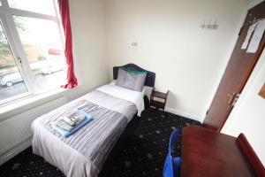 A bed or beds in a room at Avalon Guest House