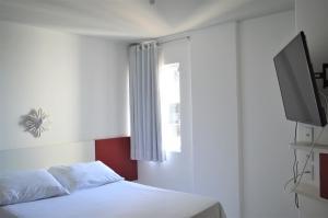 A bed or beds in a room at Apart Cote D'Azur Maceió