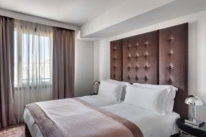 A bed or beds in a room at Lady Stern Jerusalem Hotel
