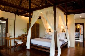 A bed or beds in a room at Kamandalu Ubud