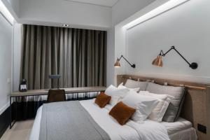 A bed or beds in a room at Niki Athens Hotel