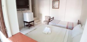 A bed or beds in a room at Pousada do Paulinho