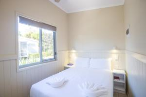 A bed or beds in a room at Fingal Bay Holiday Park