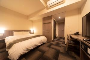 A bed or beds in a room at Dormy Inn Korakuen