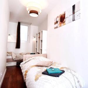"""A bed or beds in a room at 6 Couchages, Wifi Fibre & NETFLIX """"experience-immo"""""""