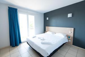 A bed or beds in a room at Zenitude Hôtel-Résidences La Tour de Mare