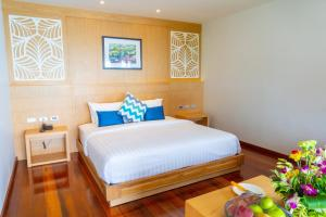 A bed or beds in a room at Coral Cliff Beach Resort Samui - SHA Plus