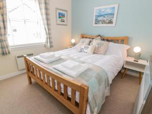 A bed or beds in a room at Grebe Cottage