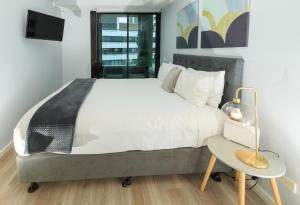 A bed or beds in a room at Waterfront Melbourne Apartments