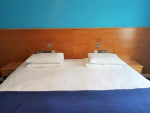 A bed or beds in a room at The Olympic Lodge