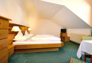 A bed or beds in a room at Hotel Dolomiten