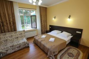 A bed or beds in a room at Hotel Kavkaz