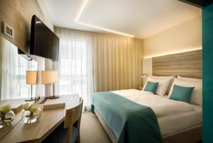 A bed or beds in a room at Hotel Marina - Liburnia