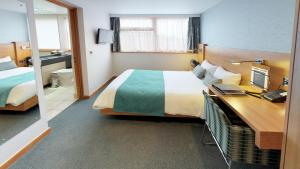 A bed or beds in a room at College Court Hotel