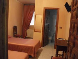A bed or beds in a room at Hostal Alfonso VI