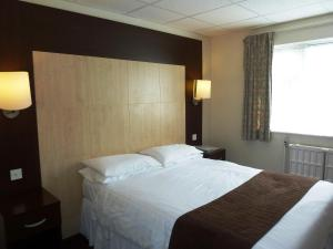 A bed or beds in a room at Lodge At Leeming Bar
