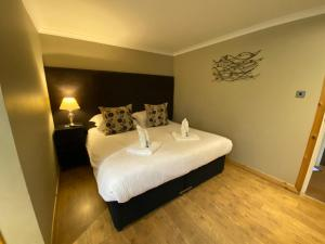 A bed or beds in a room at Auld Mill House Hotel