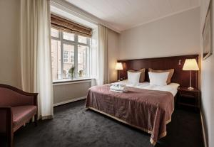 A bed or beds in a room at Ascot Hotel