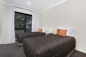 A bed or beds in a room at Wollongong Serviced Apartments