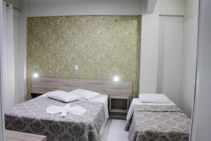 Cama ou camas em um quarto em AJ Hotel Chapecó