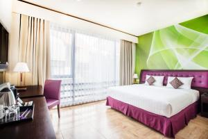 A bed or beds in a room at Kuta Central Park Hotel