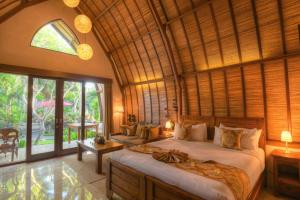 A bed or beds in a room at Klumpu Bali Resort