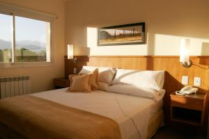 A bed or beds in a room at Urbana Class Hotel