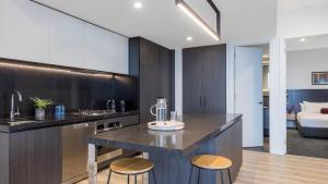 A television and/or entertainment center at Avani Melbourne Box Hill Residences