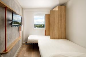 A bed or beds in a room at ibis budget Luton Airport