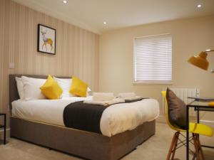 A bed or beds in a room at The Elm Serviced Apartments Camberley