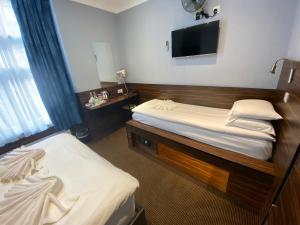 A bed or beds in a room at Crestfield Hotel