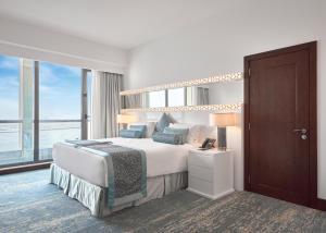 سرير أو أسرّة في غرفة في جيه ايه فندق أوشن فيو