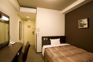 A bed or beds in a room at Hotel Route-Inn Odate Eki Minami