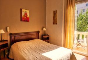 A bed or beds in a room at Au Saint Roch - Hôtel et Jardin