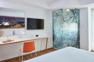 Телевизор и/или развлекательный центр в Olive Green Hotel