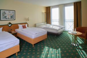 A bed or beds in a room at Balance Hotel Leipzig Alte Messe