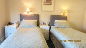 A bed or beds in a room at Hunters Lodge Guest House