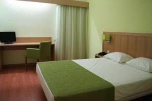 A bed or beds in a room at Viseu Garden Hotel