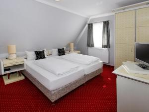 A bed or beds in a room at Hotel Kaiserworth Goslar
