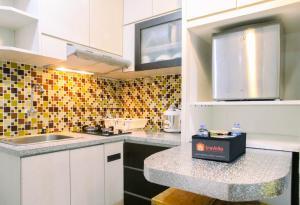 A kitchen or kitchenette at Modern Furnished 3BR at Springlake Summarecon Bekasi Apartment By Travelio