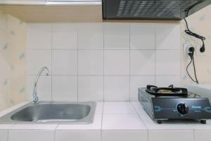 A kitchen or kitchenette at Modern Furnished Studio at Springlake Summarecon Bekasi Apartment By Travelio