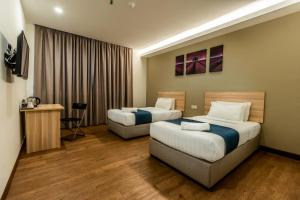 A bed or beds in a room at Orange Hotel, Sungai Buloh