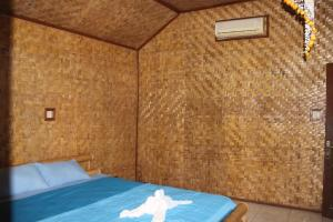 A bed or beds in a room at Penida Dive Resort