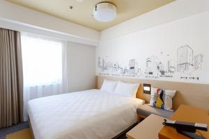 A bed or beds in a room at Shibuya Tokyu REI Hotel