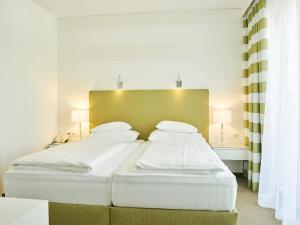 A bed or beds in a room at Werzer's Hotel Resort Pörtschach