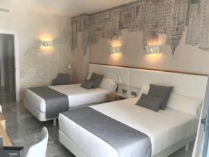 A bed or beds in a room at Hotel Madeira Centro